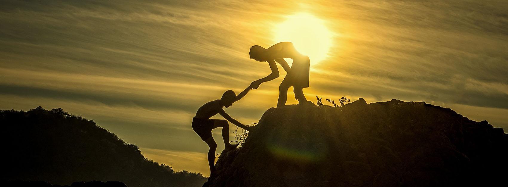 דם עוזר לאדם אחר לטפס על צוק